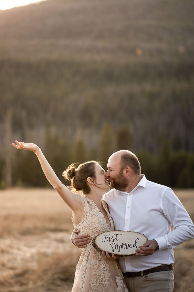 Bride and groom holding a Just Married sign in Rocky Mountain National Park in Colorado