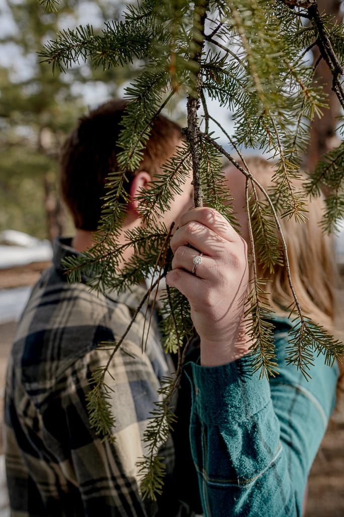 Kissing couple behind the branch of a pine tree while the woman has an engagement ring on her finger
