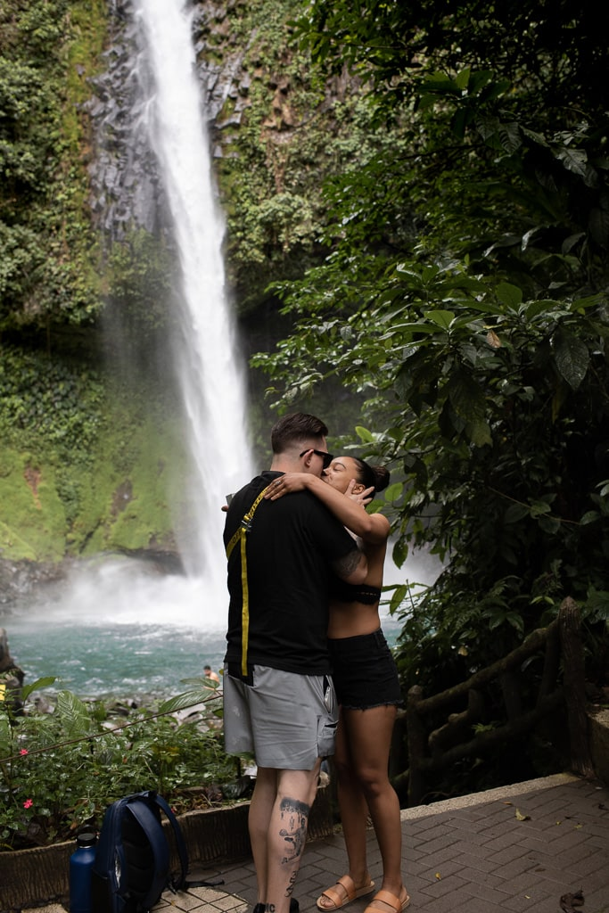 Couple who just got engaged are kissing in front of La Fortuna waterfall in Costa Rica