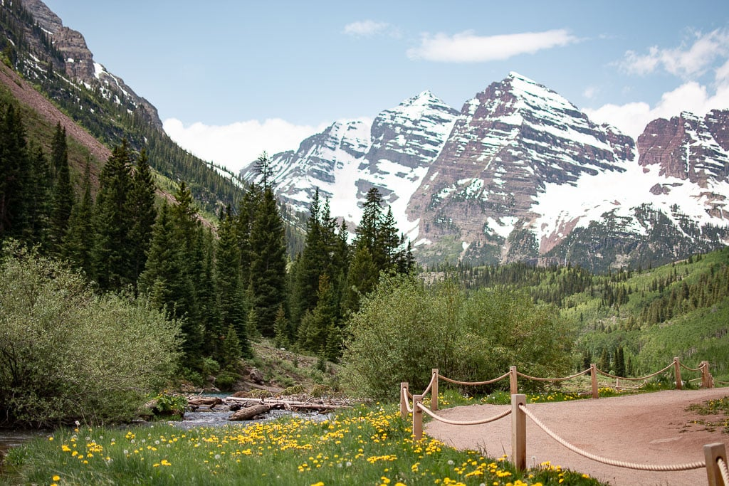 Maroon Bells near Aspen Colorado during the summer time with yellow wildflowers