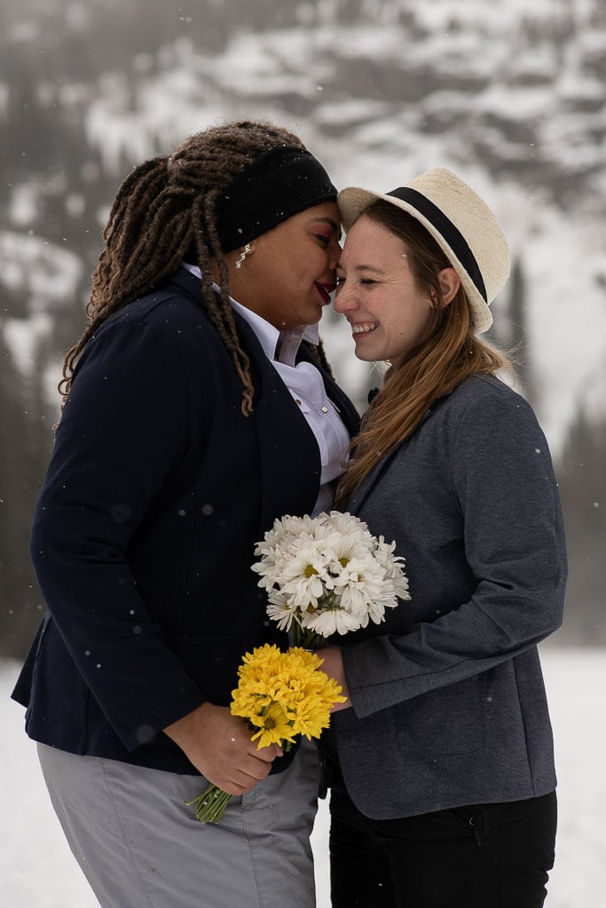 Same sex lesbian couple holding bouquets of yellow and white flowers standing in the snow and laughing