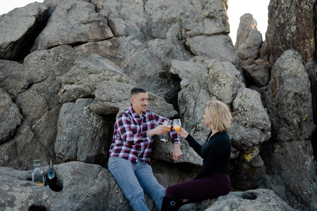 Couple sitting on big grey rock outcropping drinking mimosas to celebrate their engagement