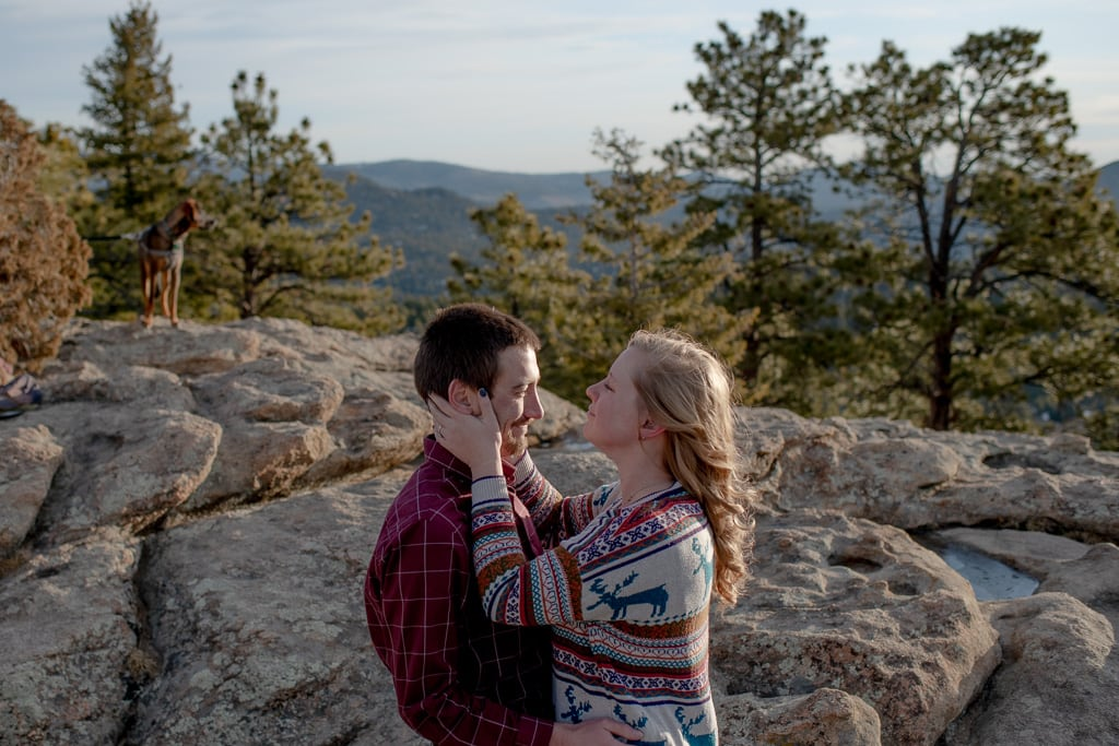 Blonde woman crying happy tears and holding the face of her new fiance while standing on a rock with mountains and trees in the distance