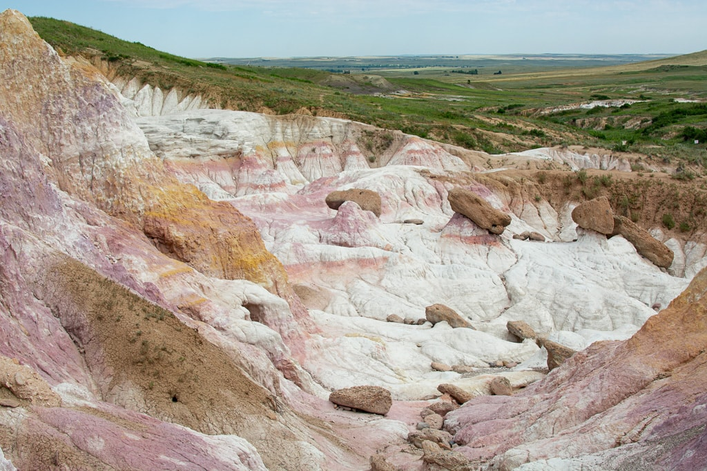 Paint mines rock formations near Colorado Springs with pink and yellow coloring and green fields in the distance