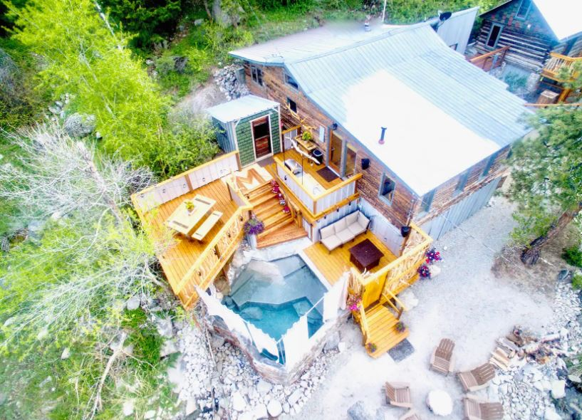 Aerial view of an Airbnb in Colorado with a natural hot spring and forest area next to a creek