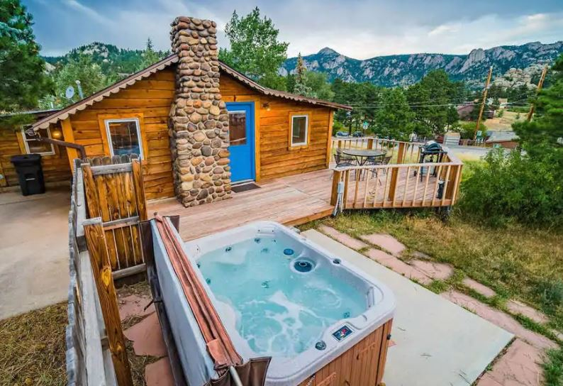 Estes Park Airbnb cabin with a stone chimney and hot tub and with mountain views in the background