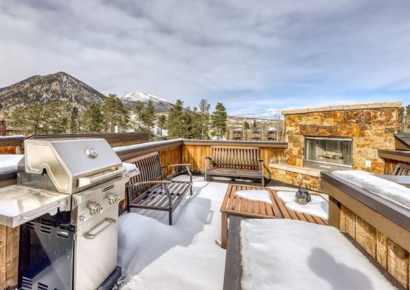 Summit County Colorado Airbnb with a rooftop patio with a grill and stone fireplace and mountain views