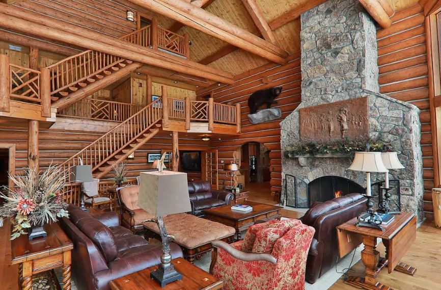 Large log home for rent with stone fireplace and leather furniture