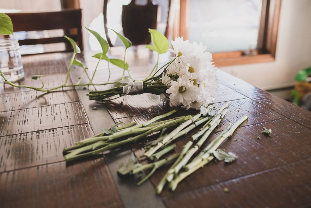 DIY elopement bouquet with white flowers sitting on a wooden table