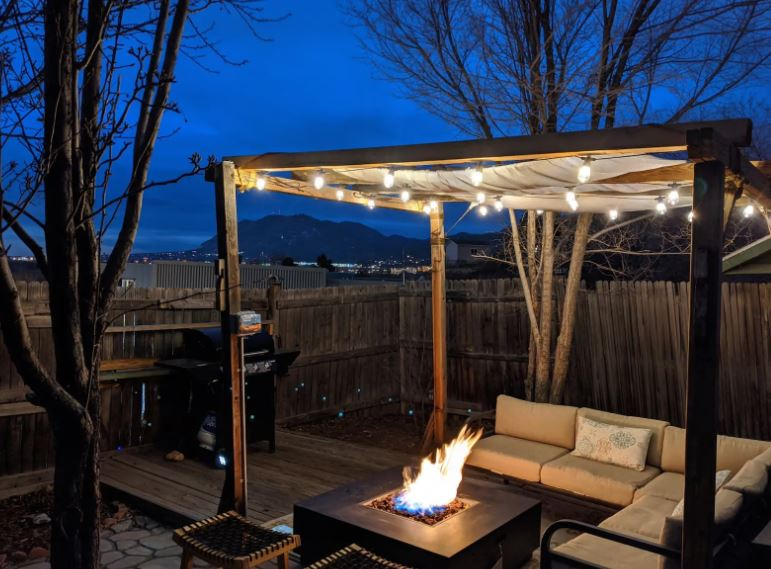 Outdoor patio with string lighting and firepit with mountains in the distance