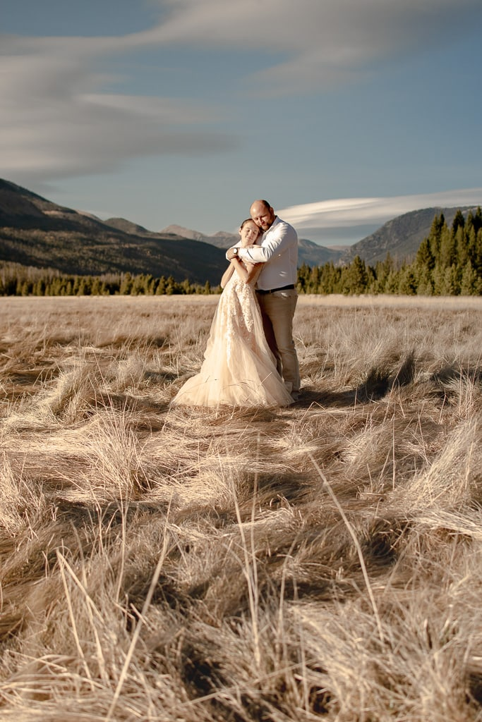 Bride and groom embracing each other in a a grassy field with mountains in the distance