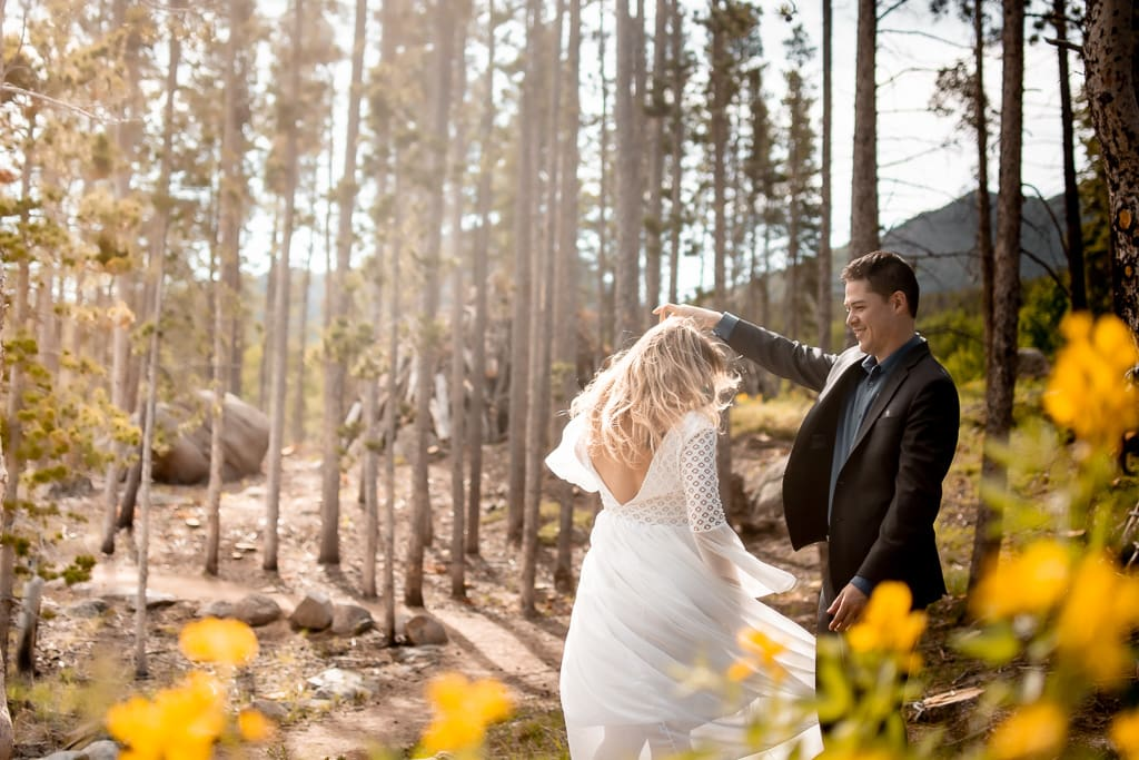 Bride and groom dancing in a pine forest with yellow flowers while the sun shines down on them