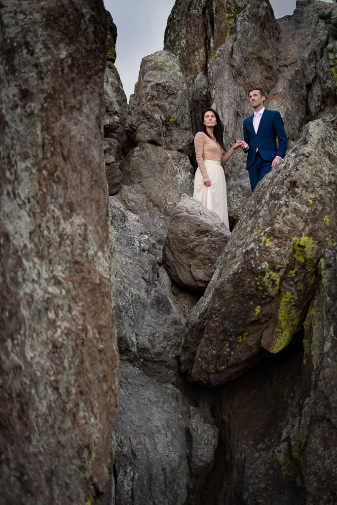 Bride and groom standing on large grey boulders and holding hands