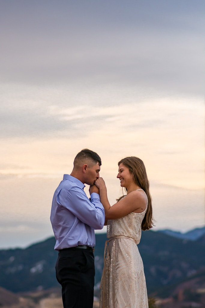 Groom kissing bride's hands at a sunrise elopement in Garden of the Gods in Colorado