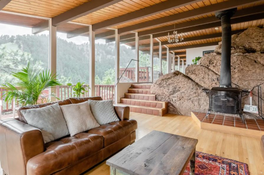 Stone fireplace in a Boulder Colorado living room with plants and a patio outside