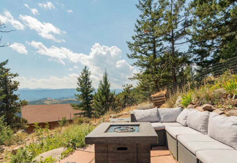 Outdoor patio with a couch and firepit with mountains in the distance near Boulder