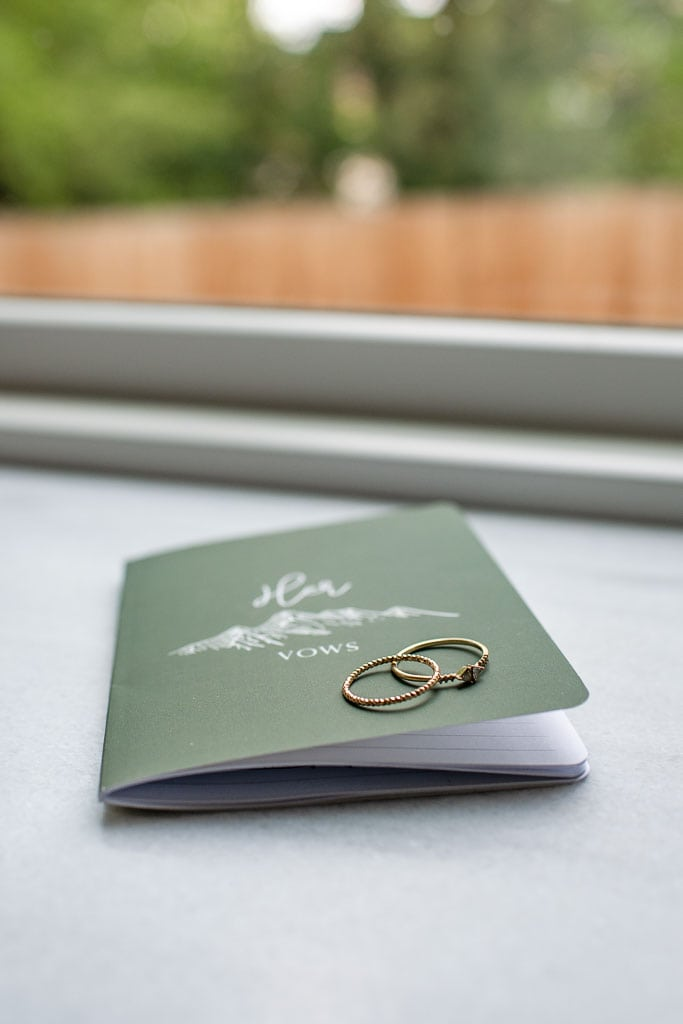 Mountain elopement vow book and wedding rings