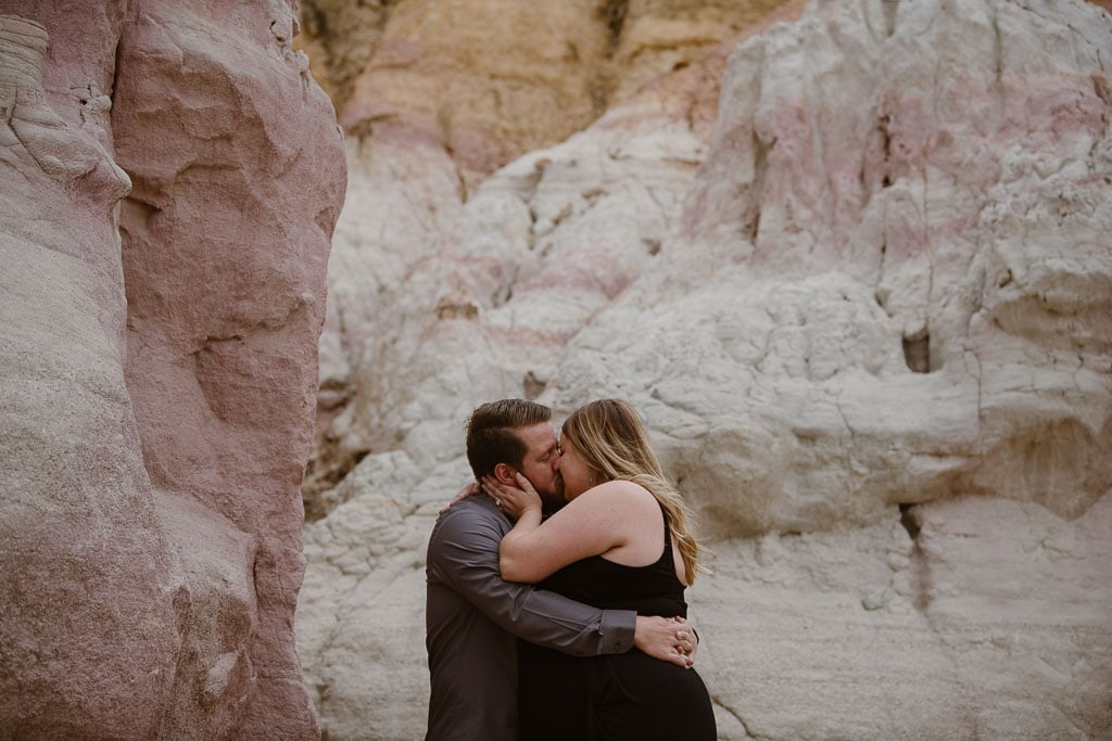 Couple embracing and kissing during their adventure elopement at the Paint Mines with pink and white rocks