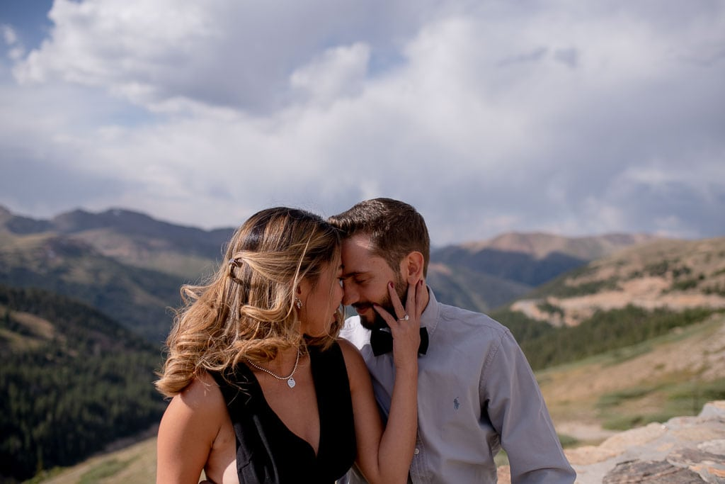 Woman holding man's face during embrace with mountains in the background of adventure elopement