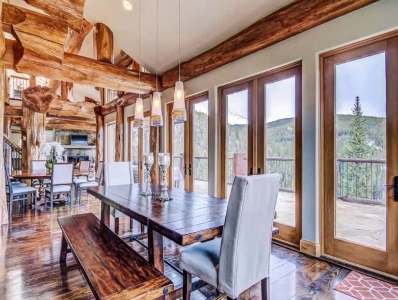 Dining room and kitchen area of a large Airbnb in Breckenridge Colorado with rustic log rafters and floor to ceiling windows
