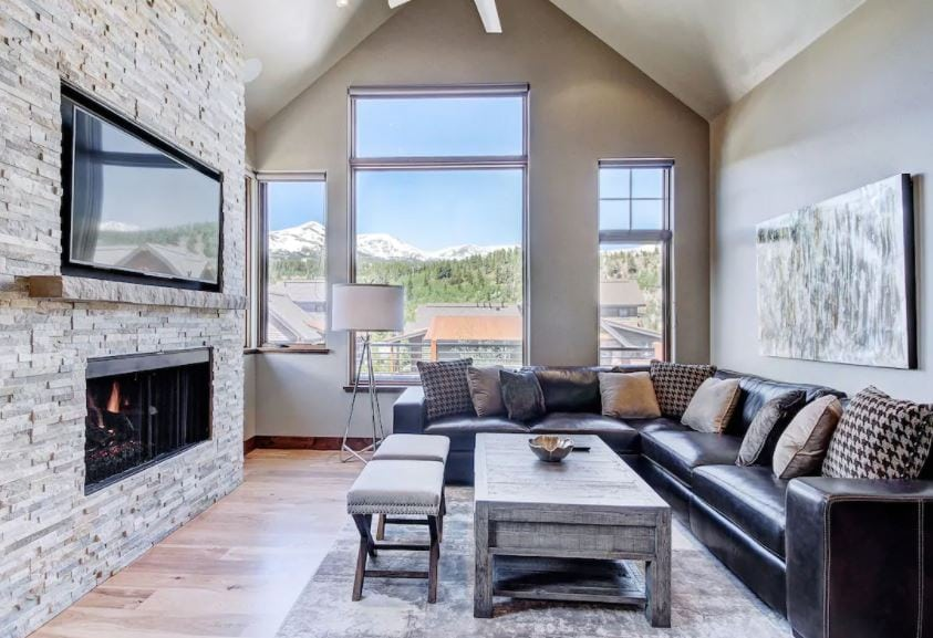 Breckenridge Airbnb modern living room with white stone fireplace, black leather couch, and mountain views out the windows