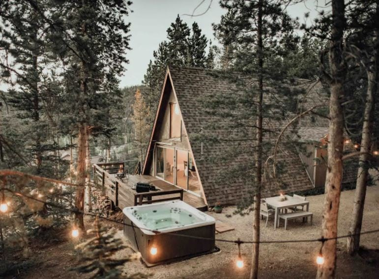 A frame Airbnb cabin in the woods with a hot tub and string lights in Breckenridge Colorado