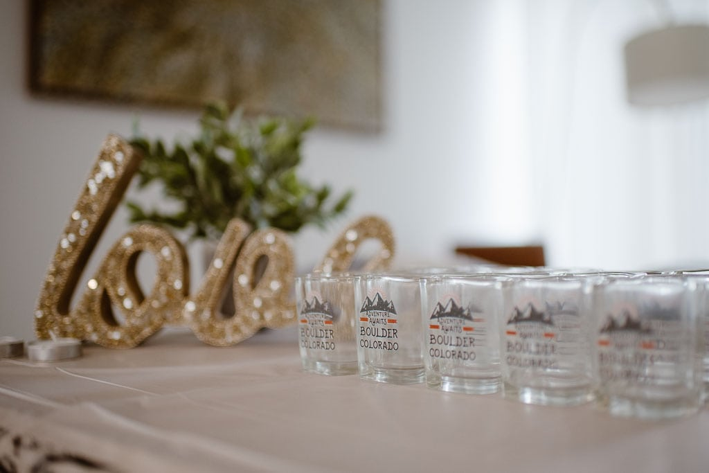 Gold, glittery LOVE sign sitting on a table next to shot glasses labeled Adventure Awaits Boulder Colorado