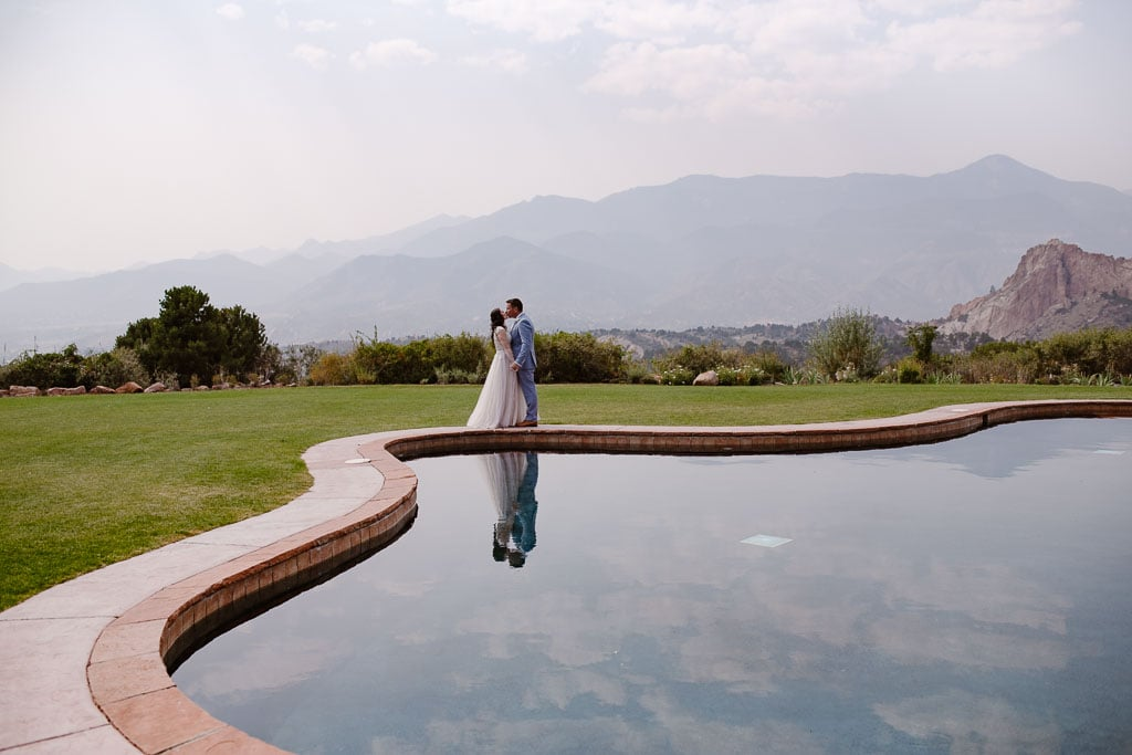 Colorado elopement photographer captures bride and groom in front of reflecting pool at Garden of the Gods resort near Colorado Springs