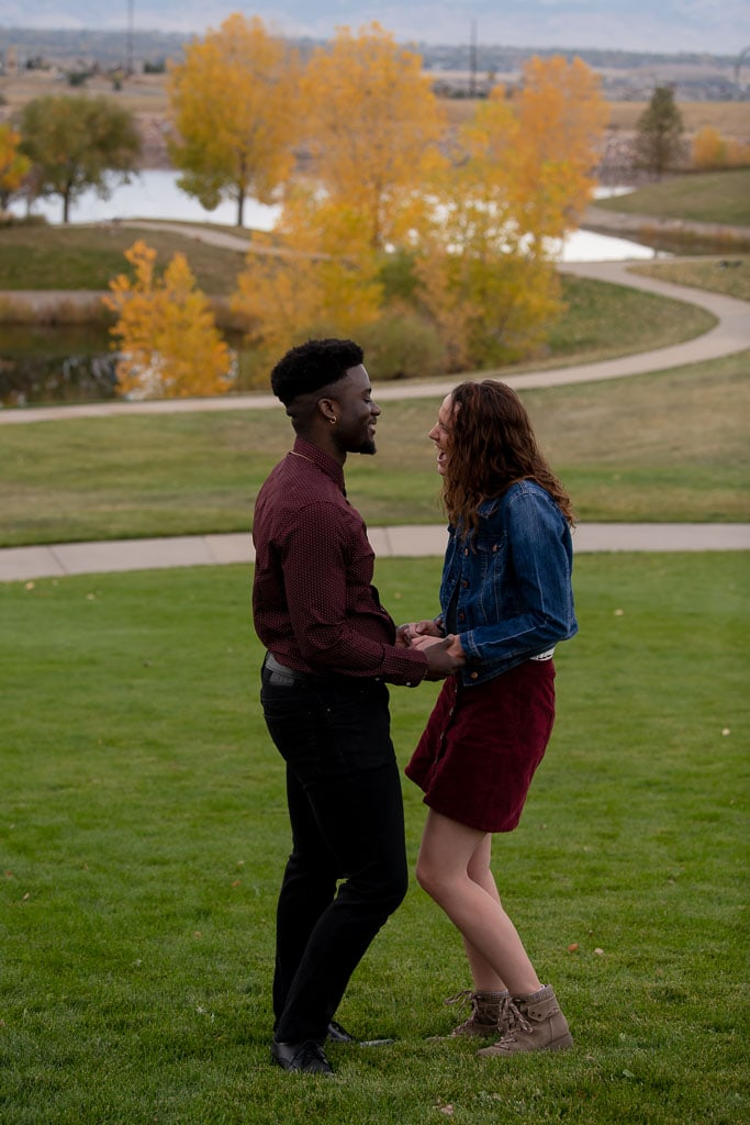 Woman laughing and smiling as man proposes to her in Colorado park