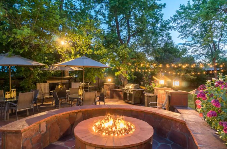 Patio backyard of Denver Airbnb with string lights and fire pit
