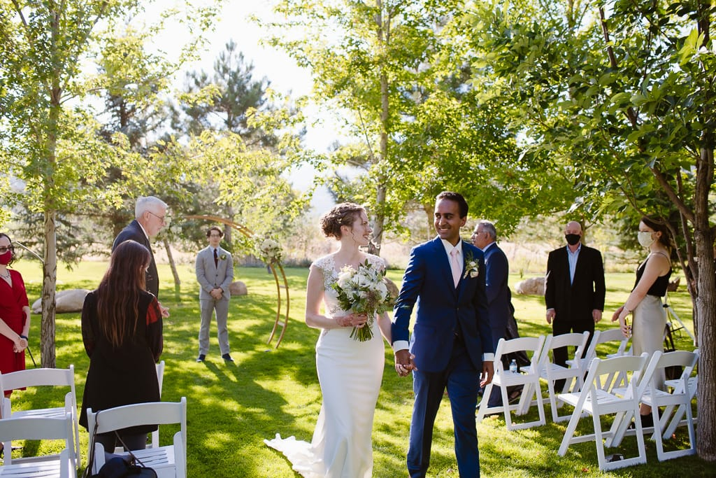 Bride and groom walking down the aisle of their backyard wedding in Colorado