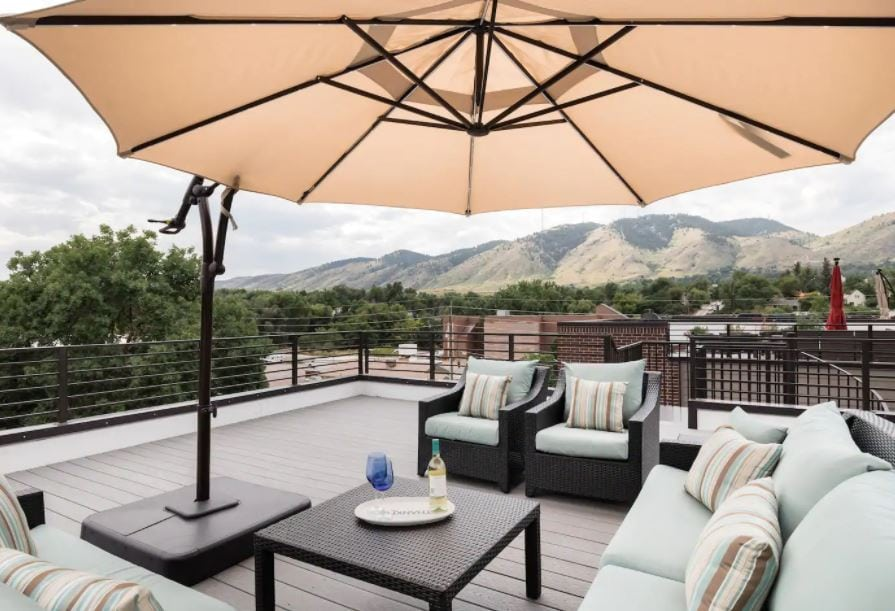Golden Colorado patio of Airbnb with outdoor furniture and foothill views