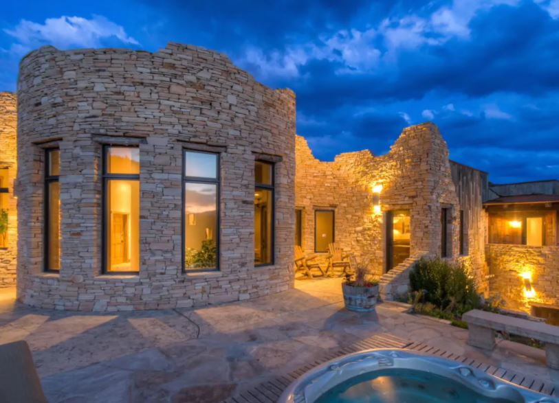 Exterior of Morrison Colorado Airbnb that has a castle-like look and hot tub on patio