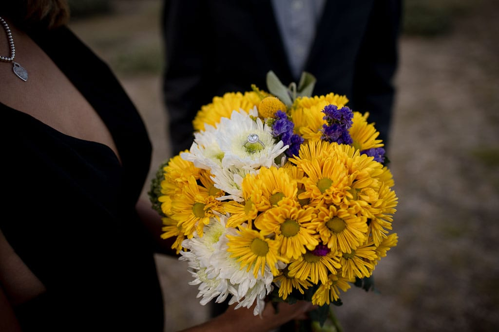 Bouquet of yellow, white, and purple flowers, held by bride with engagement ring sitting in one of the flowers