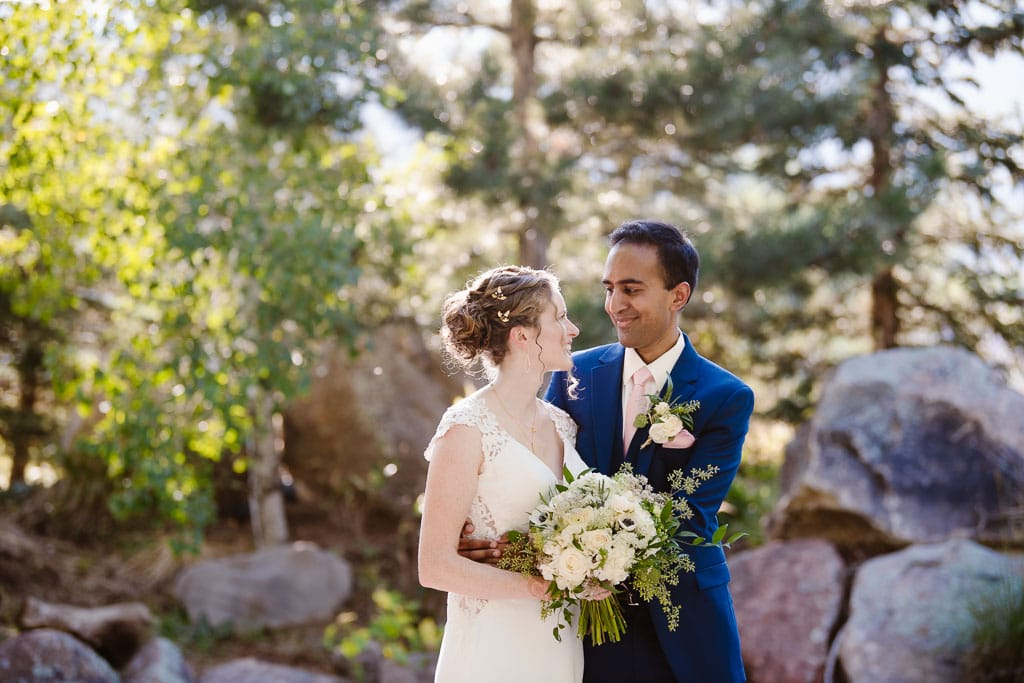 Bride and groom holding each other in front of trees and rocks
