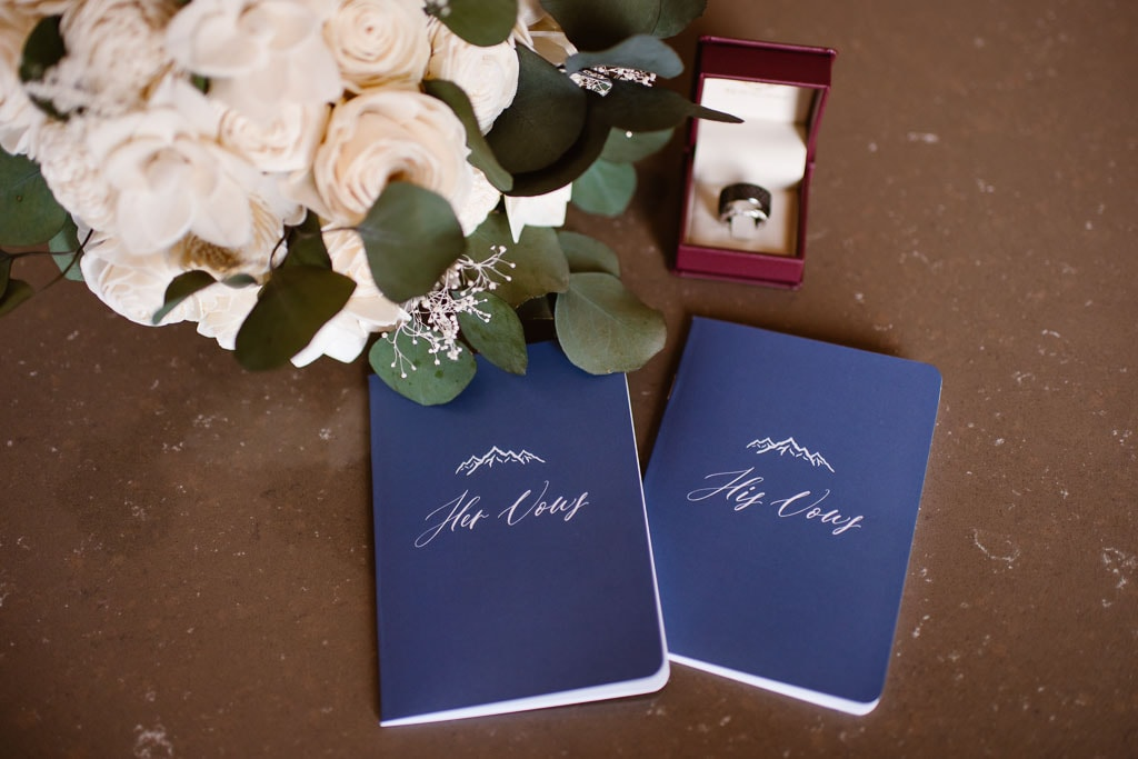 Blue his and hers vow books, bouquet and ring box sitting on a table