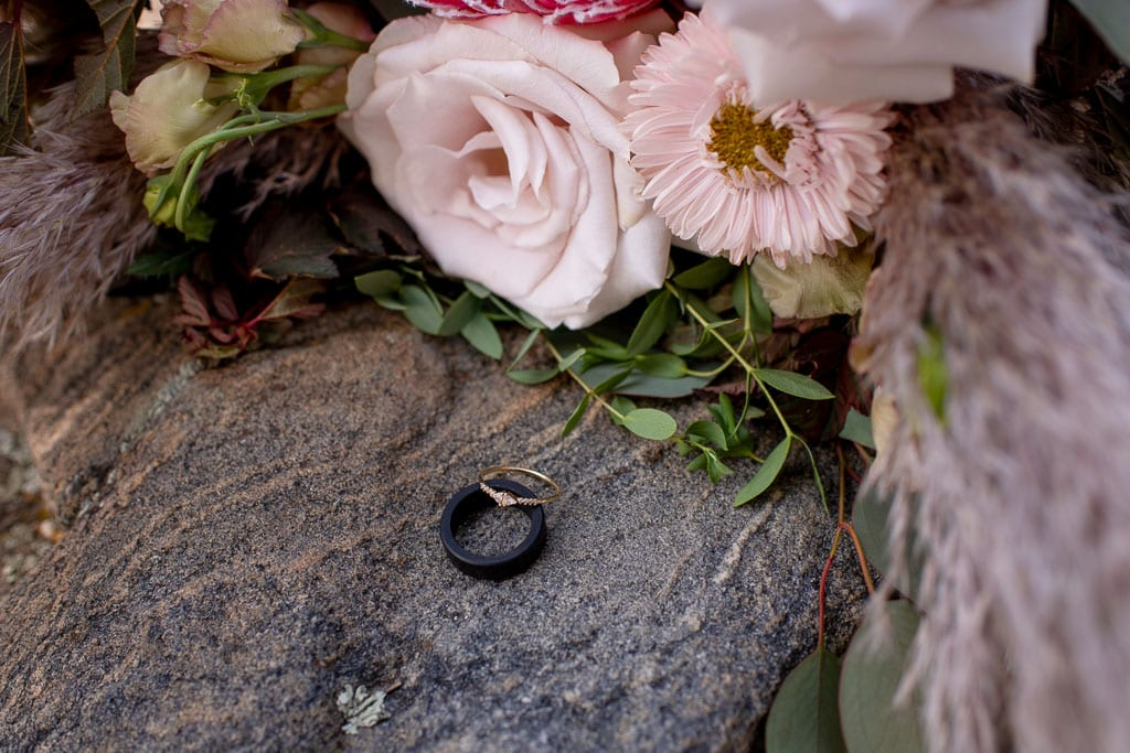Bouquet of flowers on a rock next to wedding rings for Gatlinburg elopement