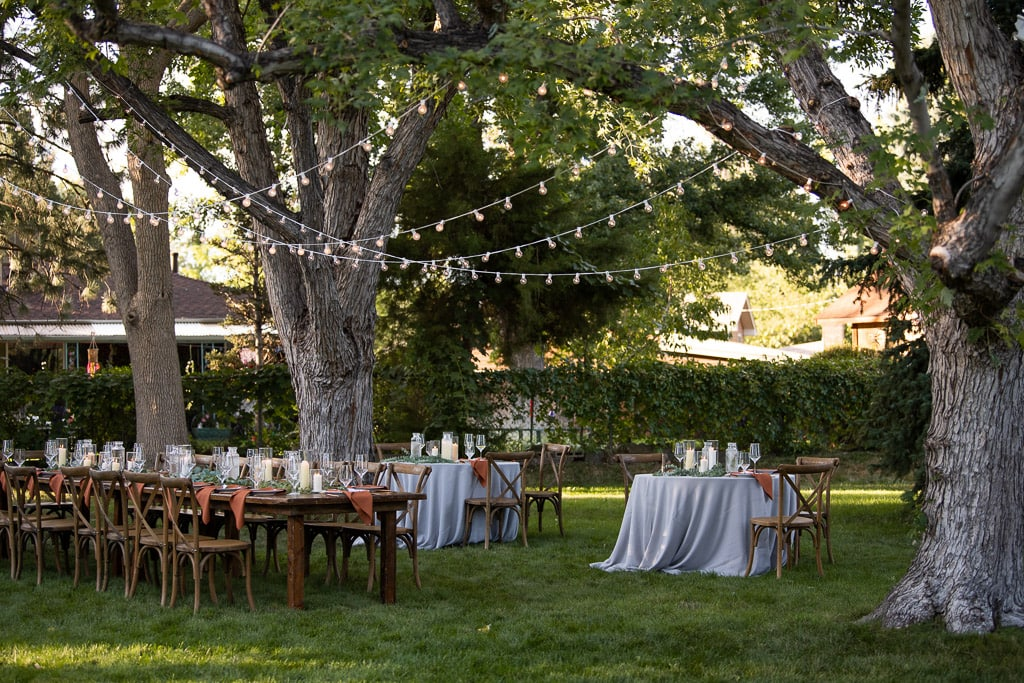Backyard wedding reception area with tables, place settings, and string lights hung from large trees