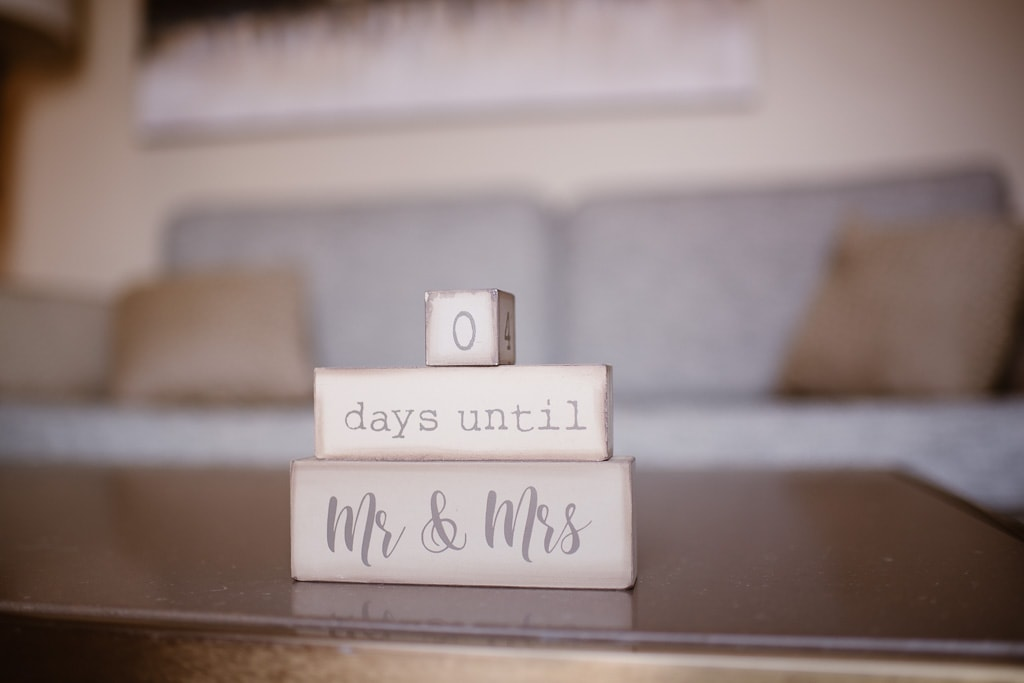 Wooden blocks on an Airbnb coffee table that count day days until Mr. & Mrs. get married