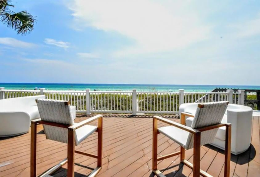 Beach patio with white chairs at a Florida Airbnb