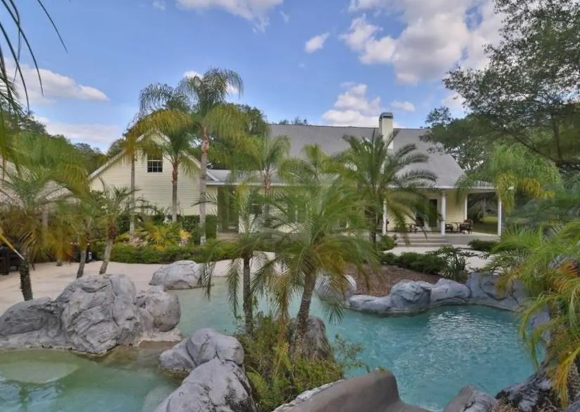 Exterior of Florida Airbnb home with a tropical pool with palm trees and large grey rocks