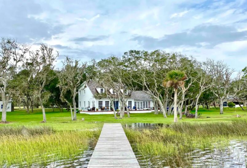 Farmhouse style Airbnb on a marsh lands with lots of trees and a wooden walkway