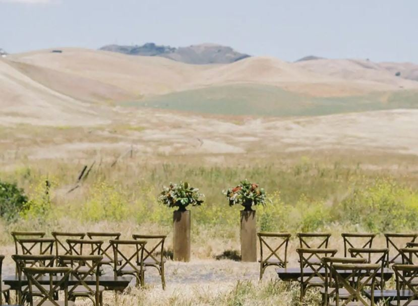 Rolling hills of Northern California with a wedding set up with chairs and flowers