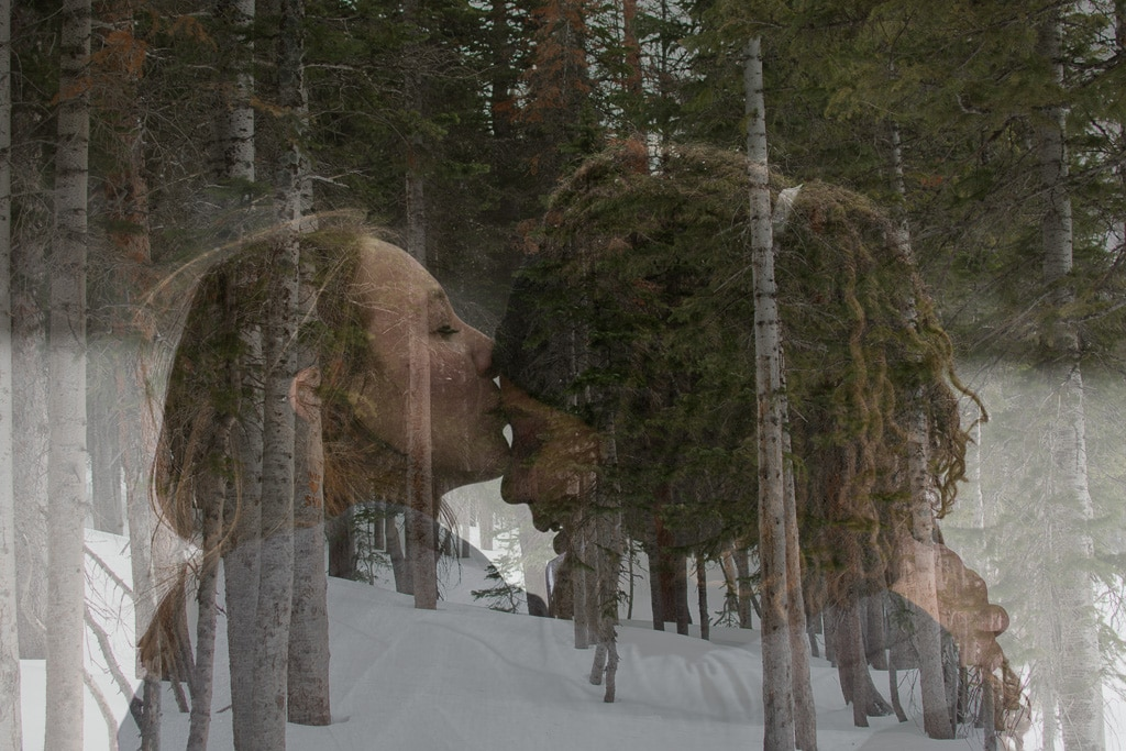 Couple kissing at their elopement in Rocky Mountain National Park with a background of snow and trees