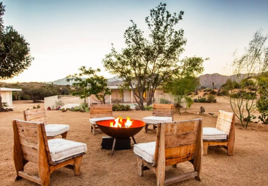 Joshua Tree Airbnb in Southern California with a firepit and chairs and mountains in the distance