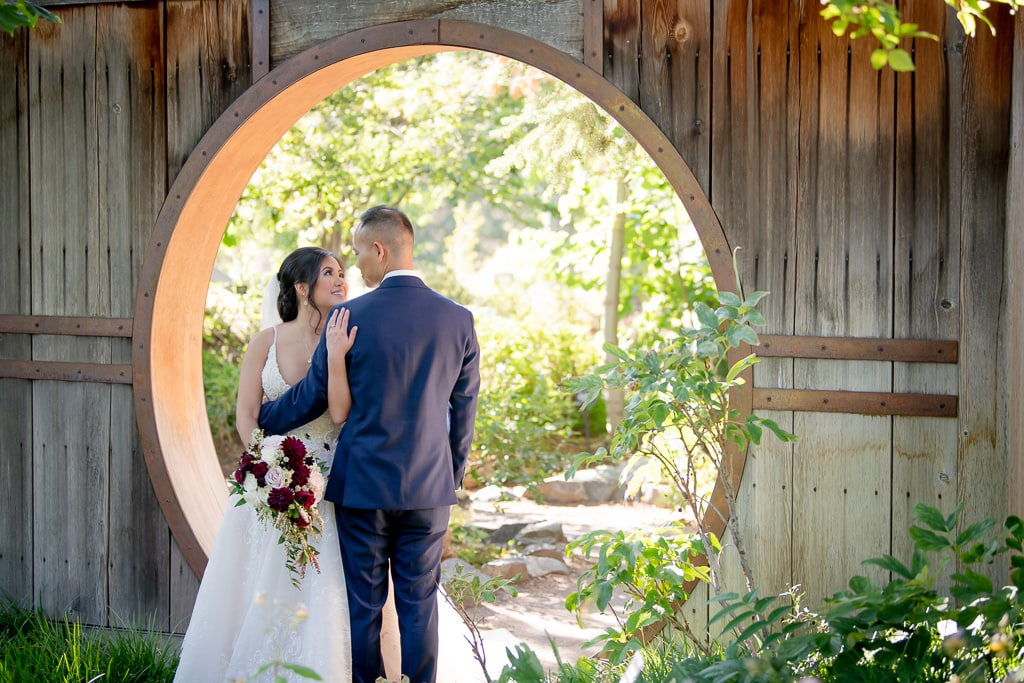 Bride and groom stand together under an arch at their Texas Airbnb Wedding
