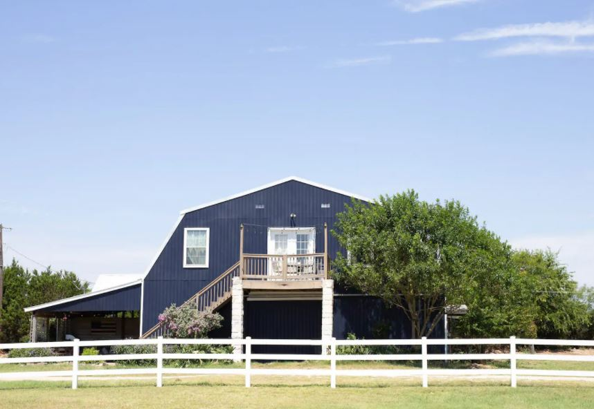 Blue barn Airbnb in Texas with a white fence and trees