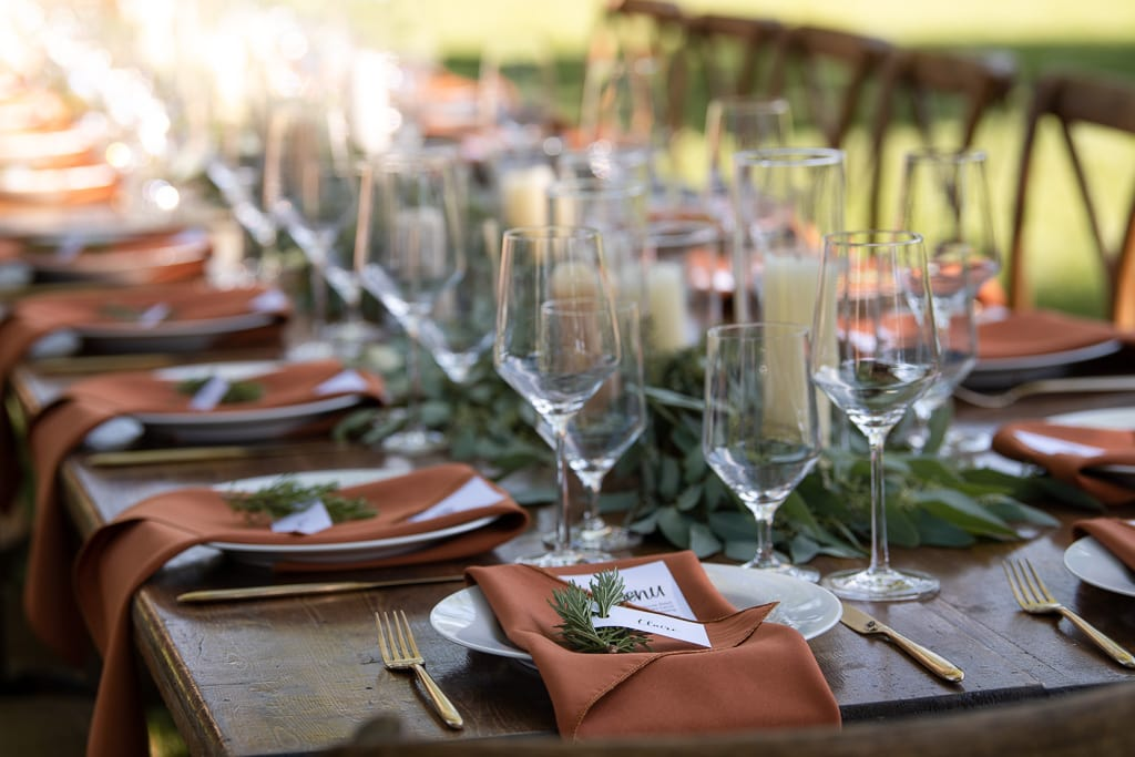 Table settings with rustic orange napkins, wine glasses, greenery, and white candles at an Aspen elopement