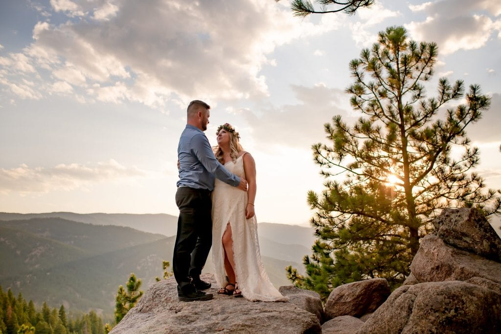 Couple eloping in Colorado with mountain views and pine trees in the distance at sunset