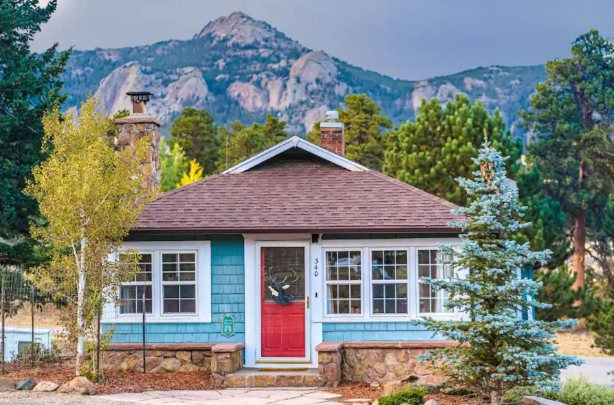 Blue cabin with a red door surrounded by trees and mountains in Estes Park Colorado